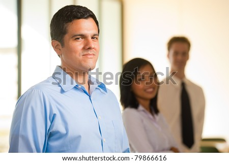 A singled out handsome hispanic male heads a line of cheerful colleagues