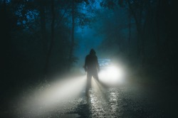 A sinister hooded figure standing in front of a car. On a spooky forest road on a foggy evening.