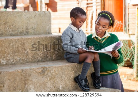 A sister are helping her little  brother with his home work.