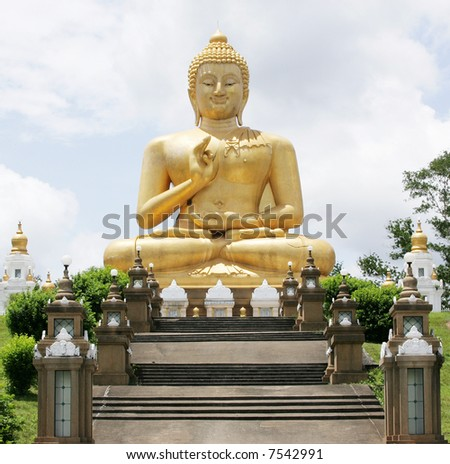 stock photo : A sitting Buddha statue against a blue sky.