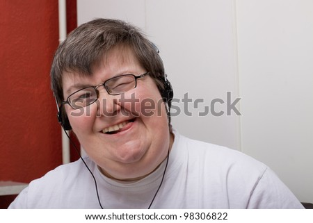 a sitting mentally disabled woman is listening to music