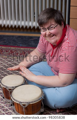 a sitting mentally disabled woman make music and looks excited