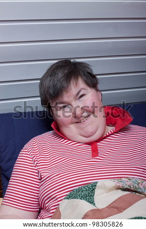 a sitting mentally disabled woman reads and smiles