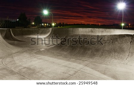 A skate park at night with lights on and sunset sky.