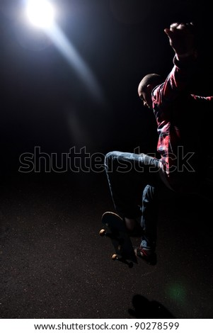 A skateboarder performs tricks under dramatic low key lighting with bright lens flare. Shallow depth of field.