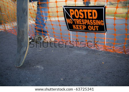 "A skateboarder steps over a fence with a sign that reads ""Posted No Trespassing Keep Out""."