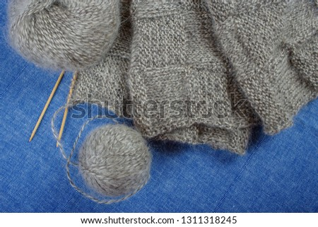 A skein and a ball of gray mohair yarn, knitted scarf and bamboo knitting needles on blue background, top view