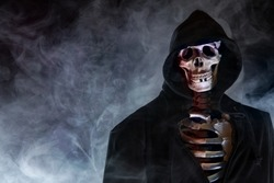 A skeleton in a cape with hood is covered with smoke
