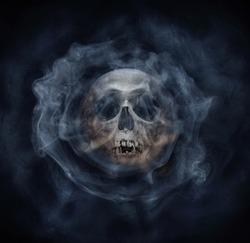 A skeleton's skull and smoke. Horror stories,  phantom,  apparition, wraith, spook phantasm background. Old gothic style.