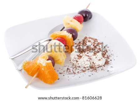 A skewer of fresh fruits with chantilly and grazed chocolate.