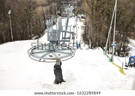 A ski lift lifts anonymous people up the slope. Russia, cloudy January day