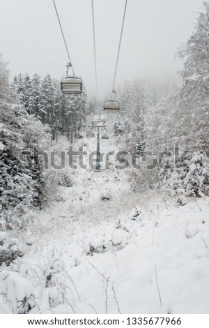 A ski lift passes over a snowy landscape surrounded by snow clad trees at a ski resort with an overcast sky #1335677966