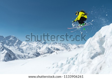 A skier in full sports equipment jumps into the precipice from the top of the glacier against the background of the blue sky and the Caucasian snow-capped mountains. Elbrus region. Russia #1133906261