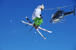 a skier in green and white performing a tele-heli, being filmed from a crew in a helicopter equipped with a front mounted steady cam