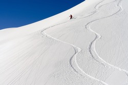 a skier makes his tracks in the deep powder snow
