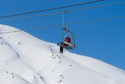 a skier on open cable car going for skking.adventrous snow game is skking.
