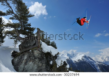 a skier performing a high jump over a rock with a gnarled pine. In the background snow covered mountains