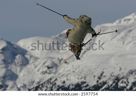 A skier styles a huge tip cross jump grabbing his ski in mid air with finesse.
