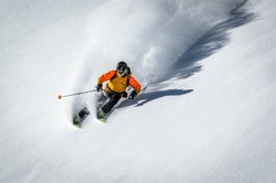A skiier making a turn in deep snow and sunshine creating a large ploom of snow and a shadow