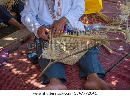 A skillful elderly handicapped man do bamboo wickerwork by hands on the floor. Showing simply way of life by self- reliance practice.