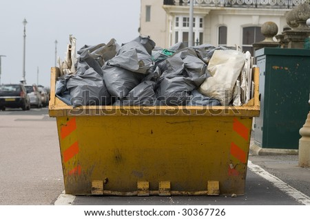 a skip full of refuse/trash sacks outside on the street
