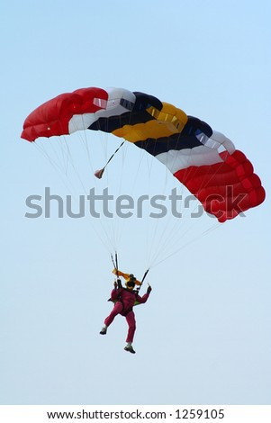 A skydiving cameraman making his way down on the parachute. - stock photo
