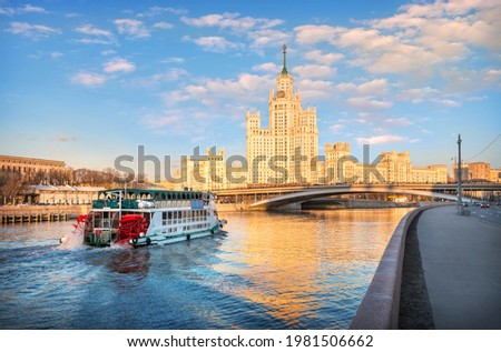 A skyscraper on Kotelnicheskaya embankment and a ship with red wheels in Moscow on a sunny spring evening Stock photo ©