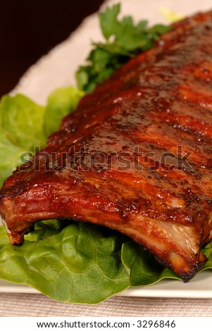 A slab of baby back barbecue ribs on a bed of lettuce