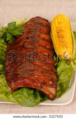 A slab of ribs resting on lettuce with an ear of roasted corn