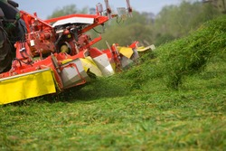 A slant angle closeup of a chopper while cutting the silage in a farmland