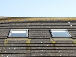 A slate roof with two velux windows