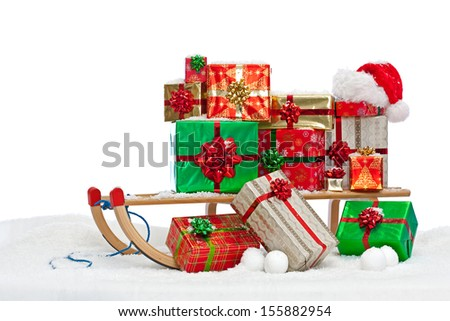 A sledge loaded with gift wrapped Christmas presents and a Santa hat, sitting on snow against a white background.