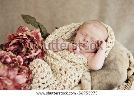 A sleeping baby girl in a basket with blankets and vintage flowers, soft focus with shallow depth of field
