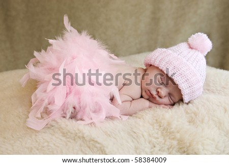 A sleeping baby girl wearing pink hat and pink feather boa, soft focus