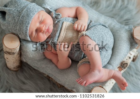 A sleeping cute newborn in a wooden bed made of birch, in a gray suit and a cap on his head