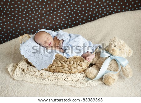 A sleeping newborn baby boy that is smiling, focus on his face, studio shot