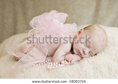 A sleeping three week old baby girl with pink bow and pearls, soft focus