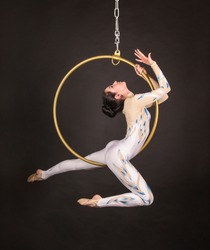 A slender,dark-haired girl - an air acrobat in a white and blue suit, performs exercises in an air ring. Studio shooting on a dark background.