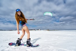 A slender girl in a bathing suit in the snow in the winter. Sportswoman snowboarding. Athlete runs a kite.