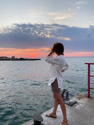 A slender girl in shorts and a white tunic stands with her back on the seashore and looks at the setting sun into the distance.