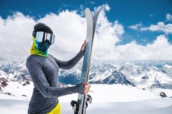 A slender skier in a ski mask and a headscarf stands in the mountains. holds skis and looks at the camera
