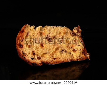 A sliace of panettone, typical italian christmass cake, in a black background