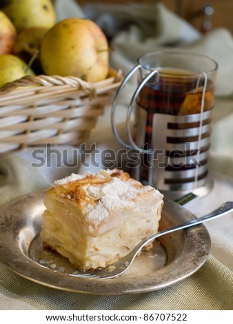 A slice of apple cake and cup of tea. Soft focus