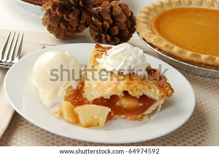 A slice of apple pie by a sweet potato pie and pine cones