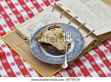 A slice of apple pie on vintage plate resting on top of very old recipe book from which it was made.
