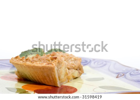 A slice of apple pie with slided kiwi, on a plate, isolated on white.