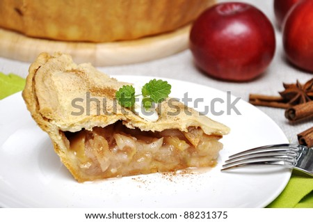A slice of apple pie with whipped cream and mint on white plate