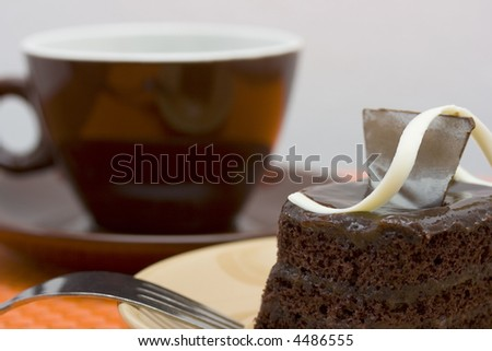 A slice of chocolate cake on a plate with a cup of coffee in the background