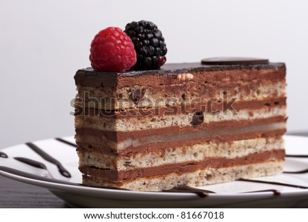 A slice of chocolate cake topped with a raspberry and blackberry on a white plate.