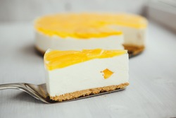 a slice of classic homemade cheesecake with a fruity yellow filling on top on a light background